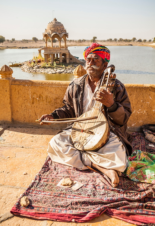 A man playing music on a Kamancha with Gadsisar Lake in the background, Jailsalmer, India.