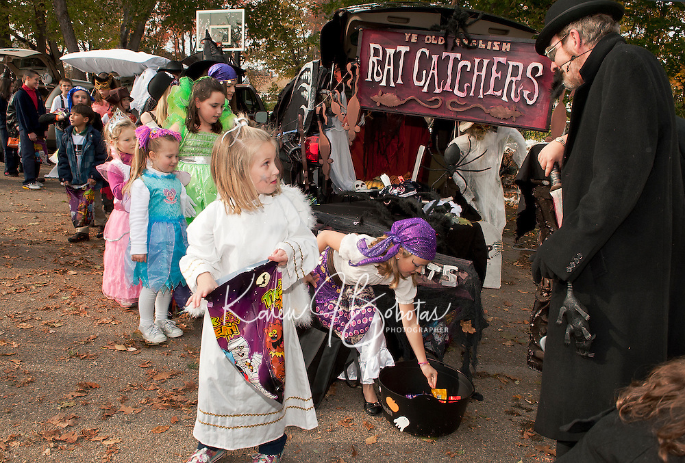 """Holy Trinity School's """"Trunk or Treat"""" was certainly a treat for Heather McKenzie as she works her way through the decorated vehicles including """"Ye Old English Rat Catchers"""" by Donna Hosmer and Joe Kildune on Monday afternoon.  (Karen Bobotas/for the Laconia Daily Sun)"""