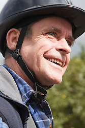 Portrait of man with visual impairment having riding lesson.