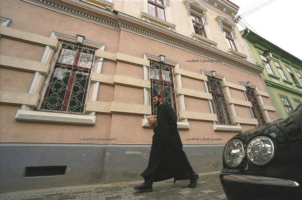 Ein Priester geht durch eine Straße von Sibiu/Hermannstadt. ..A priest walk along a sidewalk in Sibiu, Romania.