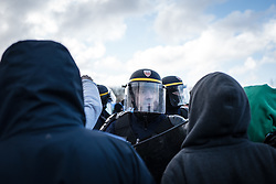 © London News Pictures. Calais, France. 07/03/16. A French CRS riot policeman remonstrates with Eritrean refugees who are to lose their shelters today. French authorities are evicting and demolishing the southern half of the Calais 'Jungle' camp, which charities estimate to contain 3,500 people. . Photo credit: Rob Pinney/LNP