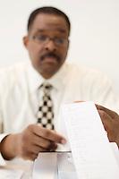 Businessman Reading an Adding Machine Tape