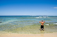 A mature man getting ready to snorkle on Ke?e Beach, North Kauai, Hawaii.