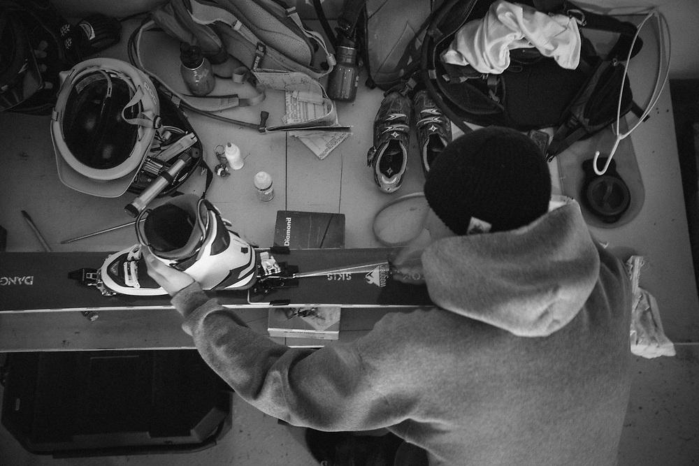 Tyler Hatcher setups touring bindings on Jay Goodrich's skis on the garage workbench.
