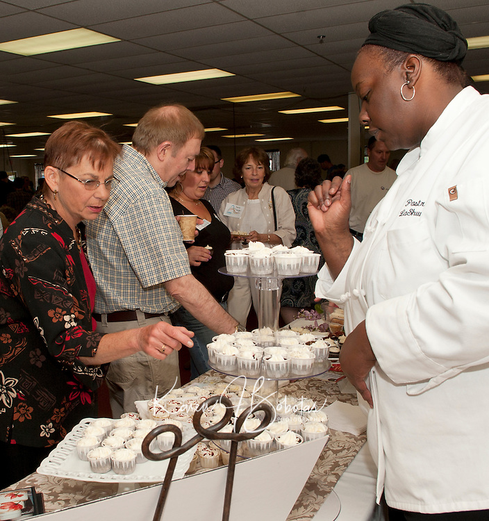 Lisa Davis selects a Coco Blackout Cake from Ooo La La's pastry chef LaShunda Allen during the 22nd annual Altrusa of Laconia's Taste of the Lakes Region event Sunday afternoon at the Conference Center at Opechee Inn and Spa.  (Karen Bobotas/for the Laconia Daily Sun)