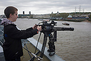 A 15 year-old teenager points a Minigun cannon from the top deck of HMS Illustrious over the river Thames at Greenwich, London. During which the Royal Navy's aircraft carrier was docked on the river, allowing the tax-paying public to tour its decks before its decommisioning. Navy personnel helped with the PR event over the May weekend, historically the home of Britain's naval fleet.