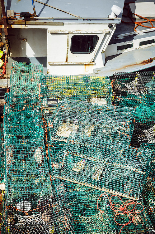Empty lobster cages stacked beside fishing boat in St-John New Brunswick, Canada