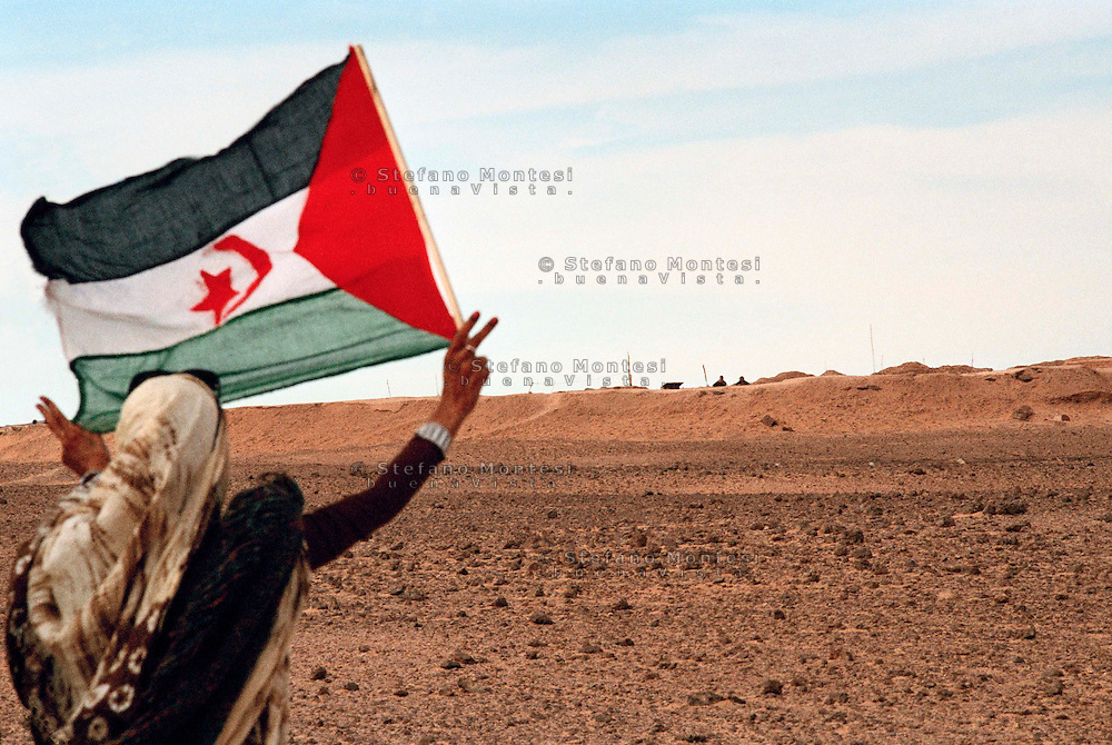 "Sahara Occidentale 15 Gennaio 2010.Una ragazza saharawi sventola la bandiera saharawi davanti al muro marocchino.Il muro marocchino o muro del Sahara Occidentale è un insieme di otto muri difensivi con una lunghezza superiore a 2.720 km costruito dal Marocco nel Sahara Occidentale. È una zona militare con bunker, fossati e campi minati, edificato con l'obiettivo di proteggere il territorio occupato dal Marocco dalle incursioni del Fronte Polisario..A girl from Western Sahara, Saharawi flag flying in front of the Moroccan Wall.The Berm of Western Sahara (also known as the Moroccan Wall) is an approximately 2,700 km-long defensive structure, mostly a sand wall (or ""berm""), running through Western Sahara and the southeastern portion of Morocco. It acts as a separation barrier between the Moroccan-controlled areas and the Polisario-controlled section of the territory that lies along its eastern and southern border."