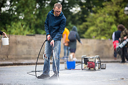 © Licensed to London News Pictures. 19/07/2019. Leeds UK. Extinction Rebellion activist's use a petrol generator to clean the road surface of Victoria Bridge in Leeds this morning on the fifth day of the protest. Activist's have blocked Victoria Bridge in the city centre with a boat & tents. The protest is part of Extinction Rebellion's 'summer uprising' campaign, which has seen similar blockades in London, Cardiff, Bristol and Glasgow & is expected to last until Friday.Photo credit: Andrew McCaren/LNP