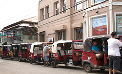 Tuk-tuks and their drivers line up to serve the incoming La Ceiba ferry, Utila, Honduras.  There are few cars and no rental cars on this semi-obscure island off the coast of Honduras in Central America.  If you don't want to walk, you take a tuk-tuk, a great and inexpensive way to get around this tiny island.