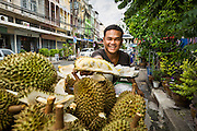 15 JULY 2014 - BANGKOK, THAILAND:  A street vendor sells durian on Samsen Soi 9 in front of the entrance to  Wat Rachathiwat Ratchaworawihan. The temple has a large teak instruction hall, considered one of the finest teak buildings in Asia.   PHOTO BY JACK KURTZ