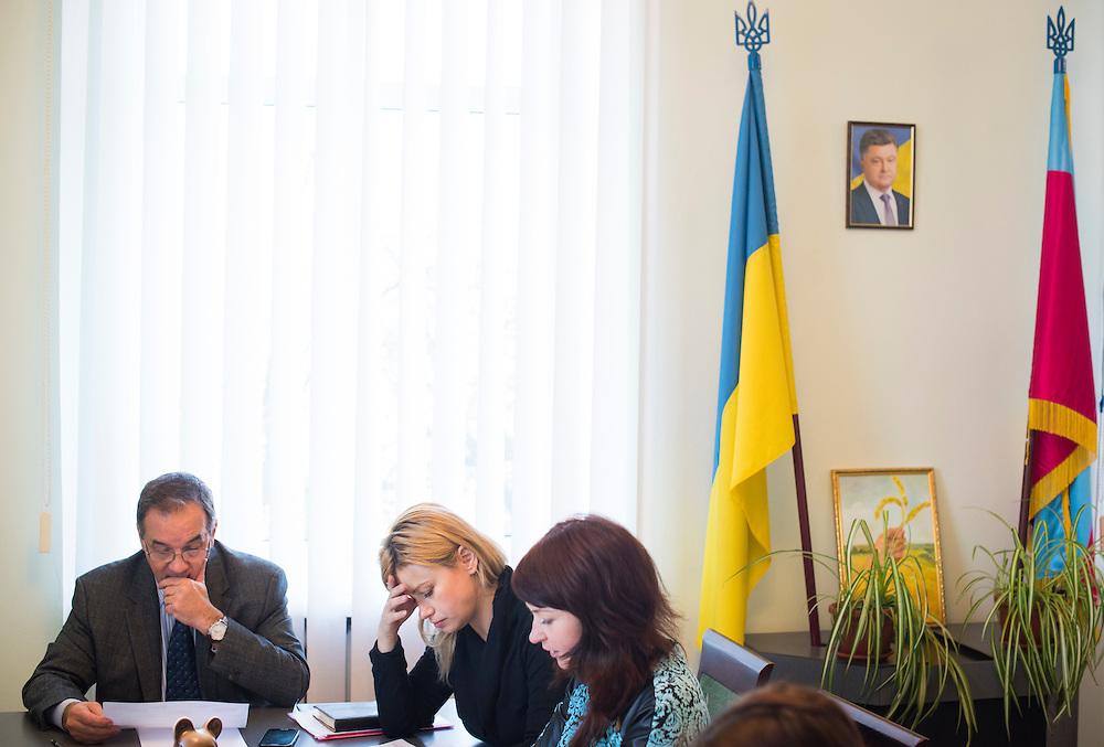 R&eacute;union entre le maire et ses plus proches collaborateurs, dans son bureau. Elena Yeskina (la blonde), son adjointe et compagne. Alyona Demicheva, son assistante. Entre les drapeaux, le portrait du pr&eacute;sident ukrainien Petro Porochenko, le 7 d&eacute;cembre 2015, Hlukhiv, Ukraine.<br /> <br /> Mayor Michel Terestchenko meets with colleagues in his office on December 7, 2015 in Hlukhiv, Ukraine. At right, between the Ukrainian and city flags, is a portrait of Ukraine's president, Petro Poroshenko.