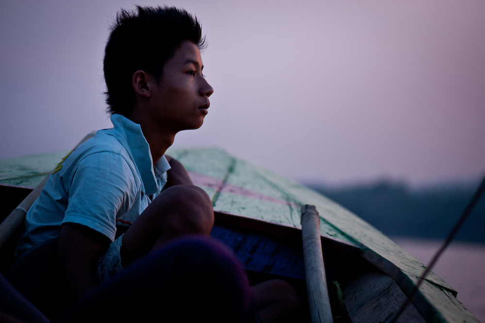 A boy watches for logs from the bow of a riverboat on the Chindwin River.