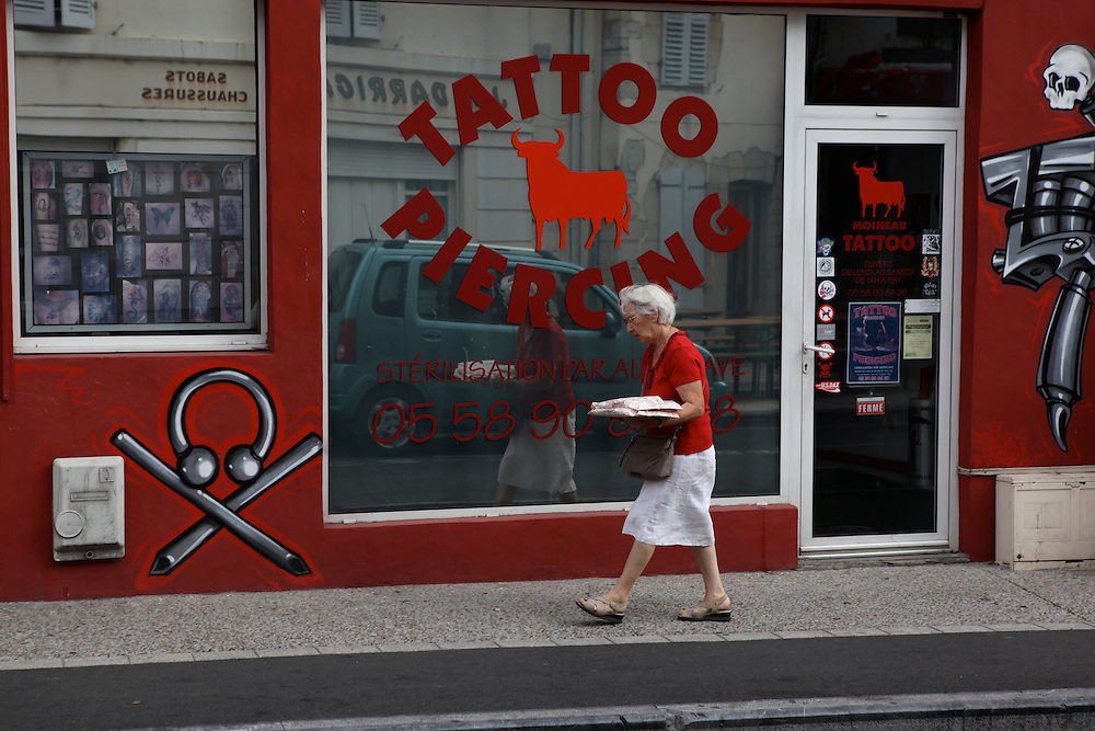 An elderly woman passes a tattoo parlour with some typical desserts from the region on the final day of the Feria du Dax.