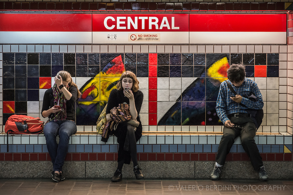Three commuters wait for a train on a bench of Central station in Cambridge, Massachusetts, while checking their mobile  devices.