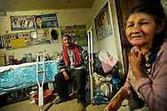 Zaccarias Mamani, 83, a lifelong coca grower, (left) attends to visiting journalists in his humble one room shack that he has decorated with several posters of President and former coca-growers union leader, Evo Morales. Mamani is an outspoken Morales supporter, saying he is the only president that has ever paid attention to poor coca growers.