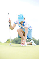 Young woman placing ball while kneeling at golf course