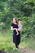Mother walking through a path on a farm holding her daughter on her hip at Meadow Mist Farm, Lexington, Massachusetts. boston family photography, boston family photographer, boston toddler photography, boston toddler photographer