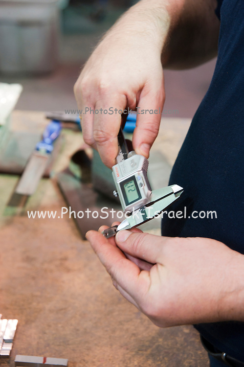 Metal tooling shop floor. Technician uses a micrometer to measure a tooled part