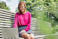 Portrait of young attractive businesswoman sitting on bench while working on her laptop