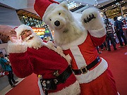 17 SEPTEMBER 2015 - BANGKOK, THAILAND: SHUKO YAMAMOTO, a Santa Claus from Japan greets the polar bear mascot for Snow Town, a theme park in Bangkok. Twenty-six Santa Clauses from around the world are in Bangkok for the first World Santa Claus Congress. The World Santa Claus Congress has been an annual event in Denmark since 1957. This year's event, hosted by Snow Town, a theme park with a winter and snow theme, hosted the event. There were Santas from Japan, Hong Kong, the US, Canada, Germany, France and Denmark. They presented gifts to Thai children and judged a Santa pageant. Thailand, a Buddhist country, does not celebrate the religious aspects of Christmas, but Thais do celebrate the commercial aspects of the holiday.    PHOTO BY JACK KURTZ
