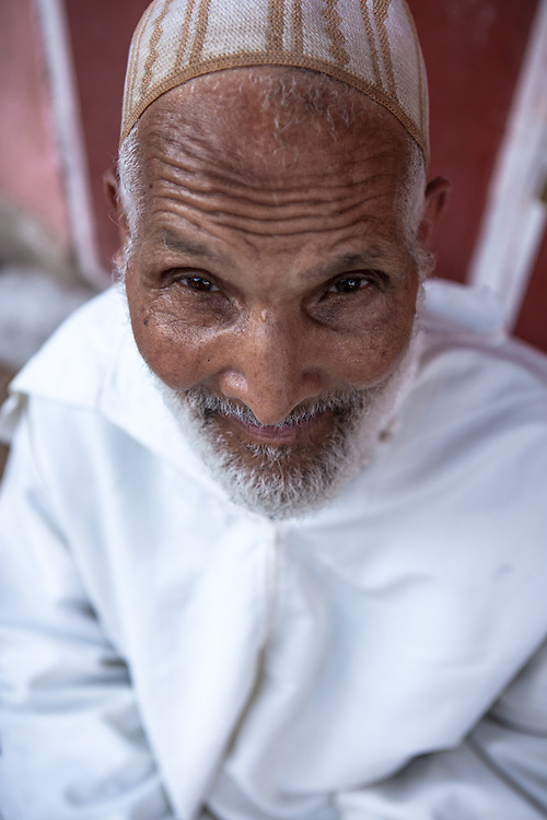 An old muslim man, wearing a traditional white djellaba, in the old medina of Marrakech, Morocco.