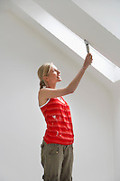 Woman painting sloping ceiling
