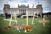 """Kreuze mit der Aufschrift """"Grenzen töten"""" vor dem Reichstag. Demonstranten stürmen bei dem """"Marsch der Entschlossenen"""" der Aktionskünstlergruppe Zentrum für politische Schönheit die Reichstagswiese und heben aus Protest gegen die EU-Asylpolitik über 100 symbolische Gräber aus."""