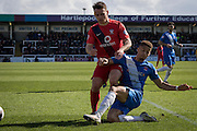 Hartlepool United defender Jake Carroll clears the ball from Reece Thompson of York City FC (22) during  the Sky Bet League 2 match between Hartlepool United and York City at Victoria Park, Hartlepool, England on 16 April 2016. Photo by George Ledger.