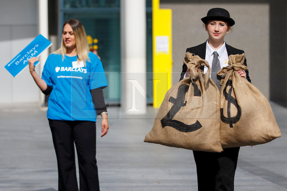© licensed to London News Pictures. London, UK 24/04/2014. A 'Robin Hood Tax' campaigner protesting against Barclays with fake money sacks during Barclays Annual General Meeting (AGM) outside Royal Festival Hall in London. Photo credit: Tolga Akmen/LNP