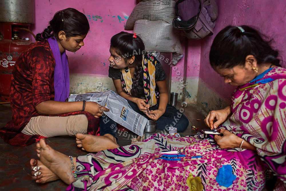 While cracking betel nut for her mother, Jyoti, 15, is trying to attract's her sister Poona's attention, as she reads a newspaper next to their mother, Sangita, 43, intent on changing a SIM card on her mobile, as they sit on the floor or their newly built home in Oriya Basti, one of the water-contaminated colonies in Bhopal, central India, near the abandoned Union Carbide (now DOW Chemical) industrial complex, site of the infamous '1984 Gas Disaster'.