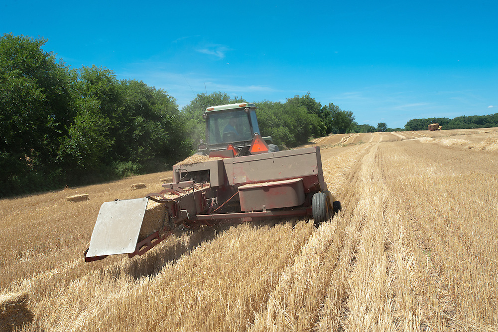 Hay baler working in field