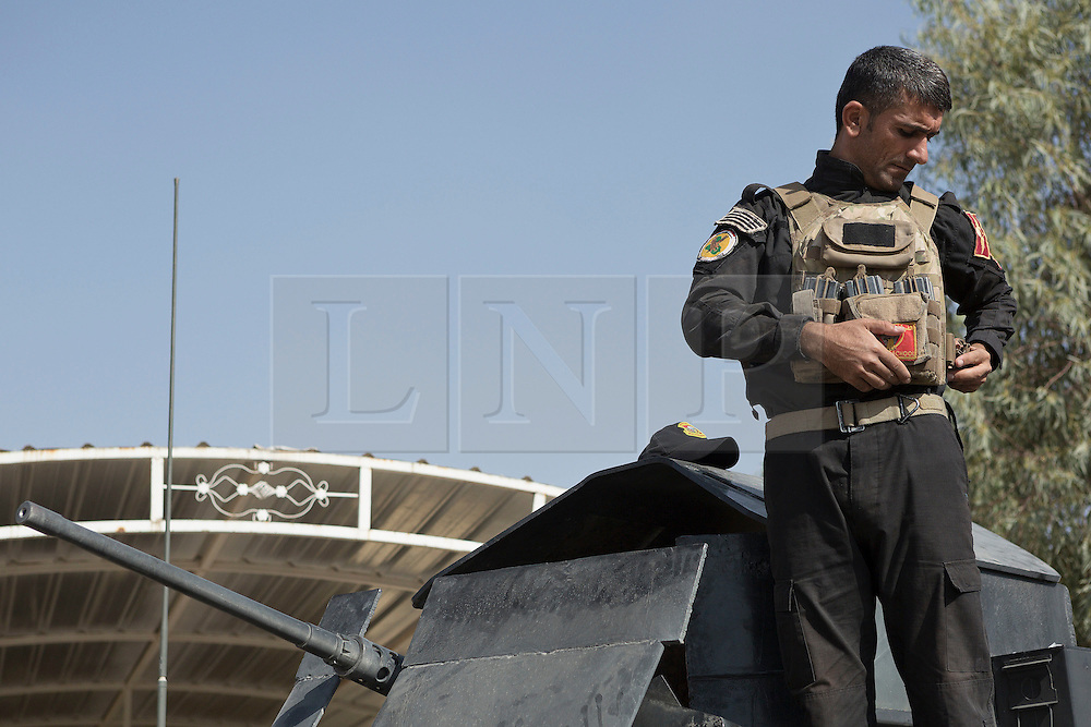 Licensed to London News Pictures. 23/10/2016. An Iraqi soldier belonging to the Counter-Terrorism group, dons his bullet proof vest as he and colleagues prepare for a trip into the nearby town of Bartella.<br /> <br /> Bartella, a mainly Christian town with a population of around 30,000 people before being taken by the Islamic State in August 2014, was captured two days ago by the Iraqi Army's Counter Terrorism force as part of the ongoing offensive to retake Mosul. Although ISIS militants were pushed back a large amount of improvised explosive devices are still being found in the town's buildings. Photo credit: Matt Cetti-Roberts/LNP