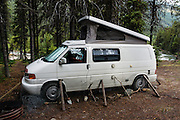 "Chicken wire, stones, and branches protect the rubber hoses on our Volkswagon Eurovan Camper from porcupines at Bugaboo Septet Recreation Site, a free campground with 4 primitive campsites operated by the Forest Service, just outside of Bugaboo Provincial Park, in British Columbia, Canada. Most tourists are attracted by nearby Canadian Rockies parks along fast paved highways and skip gravel logging roads, thereby leaving the spectacular ""Bugaboos"" as a quiet retreat for hikers, climbers, and luxury CMH helicopter guests. Directions: From Brisco (about 44 kms north of Invermere on Hwy 95), follow signs to Bugaboo Provincial Park and CMH Lodge on a gravel logging road. After 47 kms, turn right on a rougher road to reach Cobalt Lake trail head and Kain Hut trail head, or continue straight along Bugaboo Forest Service Road. Before you reach the gate of luxury CMH Bugaboo Lodge, a left turn crosses Bugaboo Creek bridge: then a left reaches Bugaboo Septet Recreation Site (reachable by 2WD vehicles) or straight up takes 4WD vehicles and hikers to Chalice Creek trailhead."