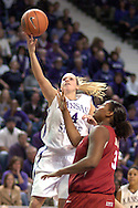 Kansas State guard Claire Coggins (L) scores past Oklahoma's Courtney Paris (R), during the second half at Bramlage Coliseum in Manhattan, Kansas, February 21, 2006.  The 9th ranked Sooners defeated K-State 78-64.