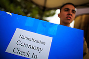 04 JULY 2012 - PHOENIX, AZ: EPHRAIM ALZARDO, a volunteer, holds up a sign directing soon to be new citizens to the check in area at South Mountain Community College Wednesday. About 250 people, from 62 countries, were naturalized as US citizens during the 24th Annual Fiesta of Independence naturization ceremony at South Mountain Community College in Phoenix Wednesday. The ceremony was presided over by the Honorable Roslyn O. Silver, Chief United States District Court Judge.    PHOTO BY JACK KURTZ