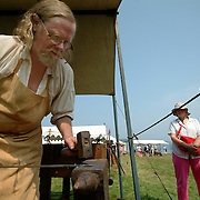 August 25, 2007 -- PHIPPSBURG, Maine.  Jeff Miller of Charlestown NH, works on a piece of iron at the celebration of the 400th anniversary of the Popham Colony on Saturday. He is working from a Temporary Forge, made from wood, because he believes that smiths working at the Popham Colony would probably have worked from a small forge like this one, due to the size and newness of the colony. Miller is a full-time Blacksmith who works in iron in methods consistent with the 17th Century. While working, he answers questions and explains his tools, methods and materials to onlookers. Miller has worked with iron as a historically accurate blacksmith for over 30 years. .On Friday and Saturday The Society of the 17th Century, an organization of 17th and 18 Century re-enactors of which Miller is a member, provided a sense of what life might have been like in the Popham Colony -- which was founded in 1607 in present day Phippsburg. While the colony lasted less than a year, it was one of the first steps towards establishing permanent settlements of Europeans in North America. Photo by Roger S. Duncan.