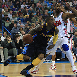 28 January 2009:  Denver Nuggets guard J.R. Smith (1) drives past New Orleans Hornets center Hilton Armstrong (12) during a 94-81 win by the New Orleans Hornets over the Denver Nuggets at the New Orleans Arena in New Orleans, LA. The Hornets wore special throwback uniforms of the former ABA franchise the New Orleans Buccaneers for the game as they honored the Bucs franchise as a part of the NBA's Hardwood Classics series. .