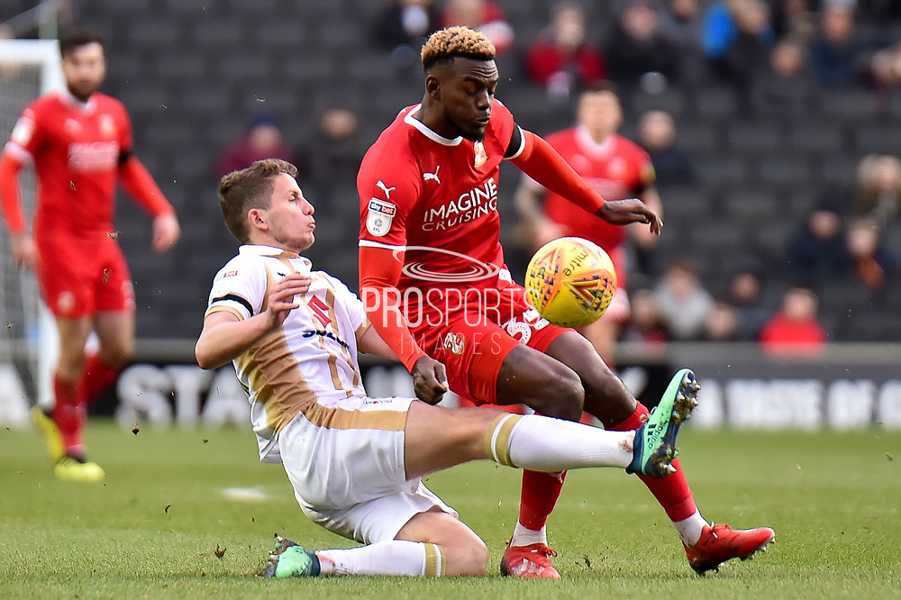 Milton Keynes Dons midfielder (on loan from Chelsea) Jordan Houghton (24) slides in to tackle Swindon Town forward Theo Robinson (35) during the EFL Sky Bet League 2 match between Milton Keynes Dons and Swindon Town at stadium:mk, Milton Keynes, England on 9 February 2019.