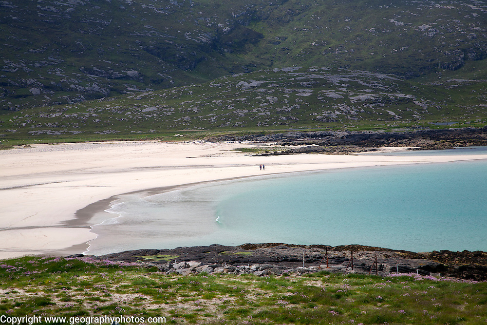 A couple walking in the distance on sandy beach in Halaman bay, Barra, Outer Hebrides, Scotland, UK