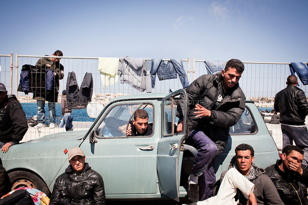 LAMPEDUSA, ITALY - APRIL 1: Tunisian migrants rest by a Renault 4 car given by a local  man in the  harbor on April 1, 2011 in Lampedusa, Italy. Thousands of people, many who left North Africa following recent unrest, are stranded on the Italian island of Lampedusa in appalling conditions.  About 22,000 immigrants have arrived on the island since January, most of them from Tunisia. with many already having been moved to other parts of Italy...Many on Lampedusa have not been provided with the most basic humanitarian assistance such as shelter, medical care, mats, blankets and access to sanitary facilities, while thousands continue to sleep outdoors...(Photo by Gianni Cipriano / Getty Images)
