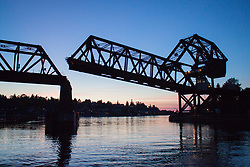 United States, Washington, Seattle. A Bascule railway bridge near the Chittenden Locks at sunset in Ballard. More technically, the bridge is a single-leaf through truss with overhead counterweight.