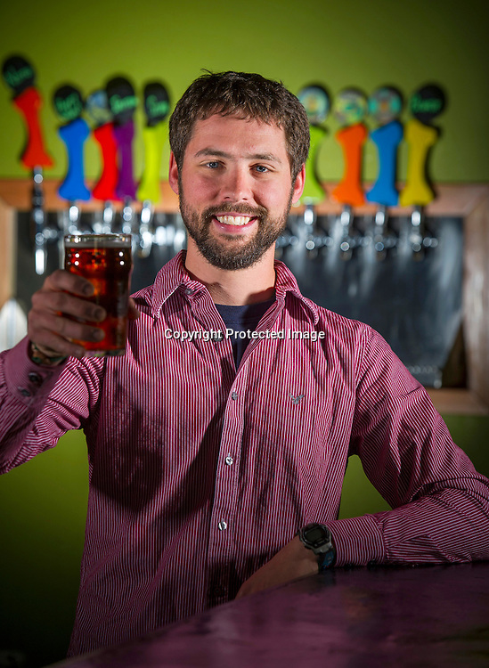 Ben Mills, owner of Fossil Cover Brewing Company holds a glass of beer while standing in his bar on Friday, March 20, 2014, in Fayetteville, Arkansas.<br /> <br /> Photo by Beth Hall