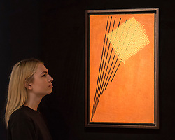 "© Licensed to London News Pictures. 25/11/2016. London, UK. A staff member views ""Construction No. 95"" by Alexander Rodchenko (est. GBP 2.5-3.5m), at the preview of artworks from Sotheby's upcoming Russian sales in New Bond Street, where over three hundred works spanning several centuries will be offered. Photo credit : Stephen Chung/LNP"