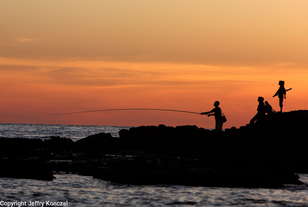A man fishes along the coast in Beirut, Lebanon with his family.