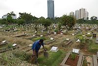 A man keeps graves clean in a Jakarta cemetery. Un homme garde les tombes propres dans un cimetiere de Jakarta.
