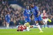 Chelsea defender Kurt Zouma (15) has his eyes on the ball as Aston Villa forward Wesley (9) lays injured during the Premier League match between Chelsea and Aston Villa at Stamford Bridge, London, England on 4 December 2019.