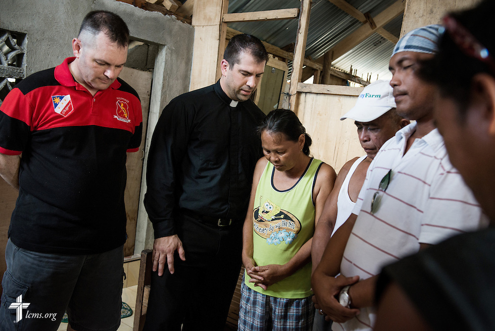The Rev. Ross Johnson, director of LCMS Disaster Response (center, left) leads a family in prayer following a meeting at their rebuilt home in Mayahag, Leyte Province, Philippines, on Saturday, March 15, 2014. Help from LCMS disaster dollars helped the family rebuild their home following Typhoon Haiyan. LCMS Communications/Erik M. Lunsford