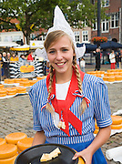 Smiling blonde young Dutch woman  traditional clothes Gouda and cheese market, South Holland, Netherlands,