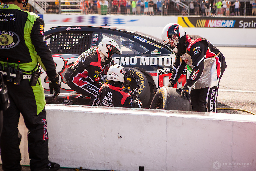 Driver Matt DiBenedetto's pit crew changes a tire during a pit stop in the NH 301 NASCAR Sprint Cup race at the New Hampshire Motor Speedway.